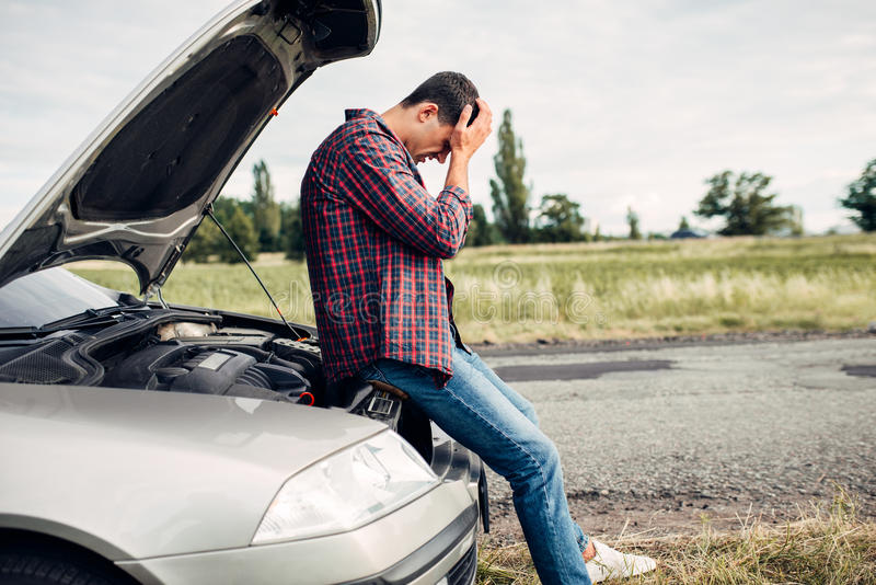 Homme déprimé s'asseyant sur un capot de voiture cassée photos stock
