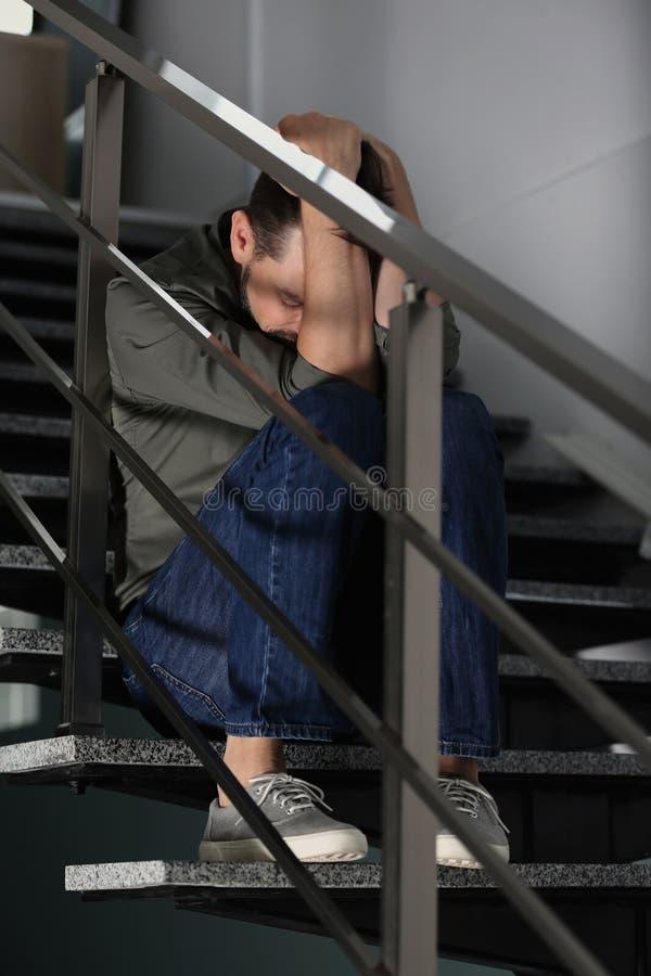 Homme déprimé seul s'asseyant sur des escaliers à l'intérieur photos libres de droits