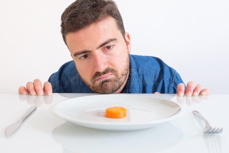 Homme déprimé suivant un régime et mangeant seulement des légumes image libre de droits
