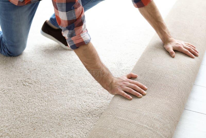 Homme déroulant le nouveau plancher de tapis images stock
