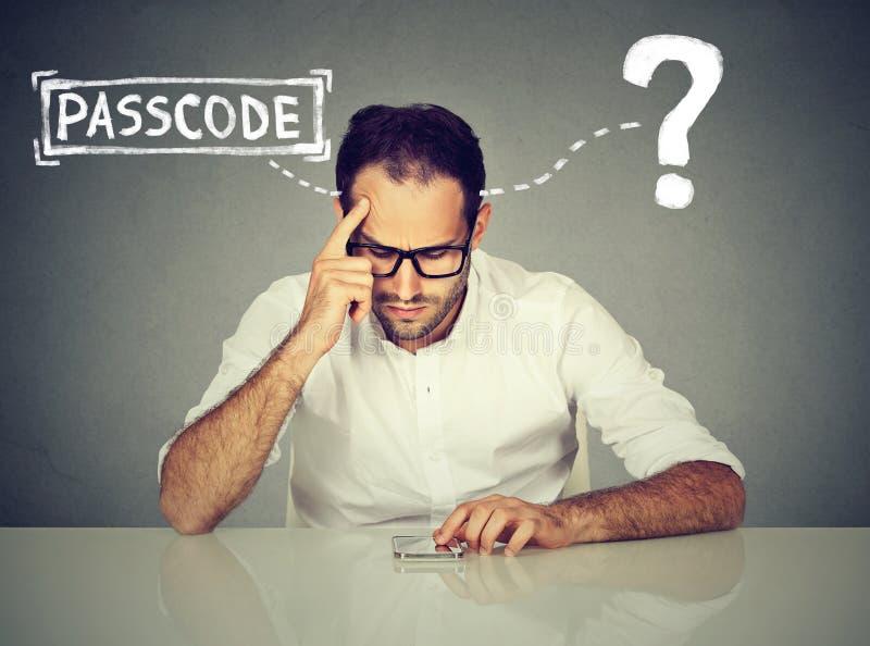 Homme désespéré essayant de noter dans son mot de passe oublié futé de téléphone image libre de droits
