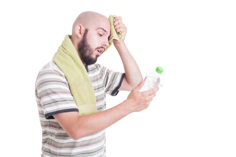 Homme déshydraté essuyant le front et tenant la bouteille de l'eau photographie stock