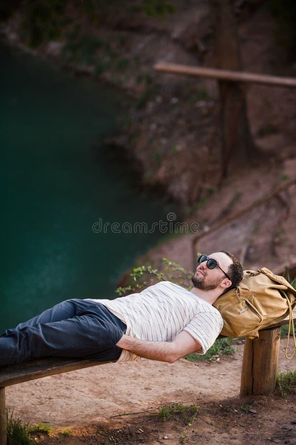Homme détendant à l'extérieur Utilisant un T-shirt blanc, le pantalon foncé, lunettes de soleil, un jeune type se couche sur le b photos libres de droits