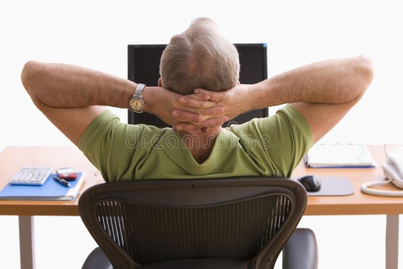 Homme détendant à son bureau image stock