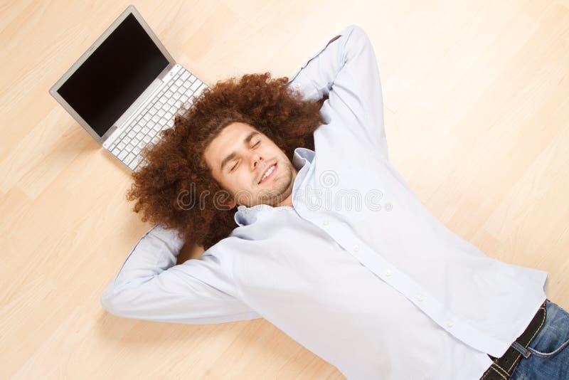 Homme détendant avec l'ordinateur portatif image stock