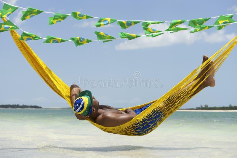 Homme détendant dans l'hamac sur la plage brésilienne image libre de droits