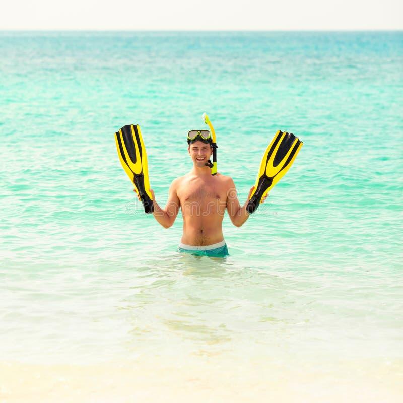 Homme, détendant dans les ailerons et le masque noirs jaunes de nageoires image libre de droits