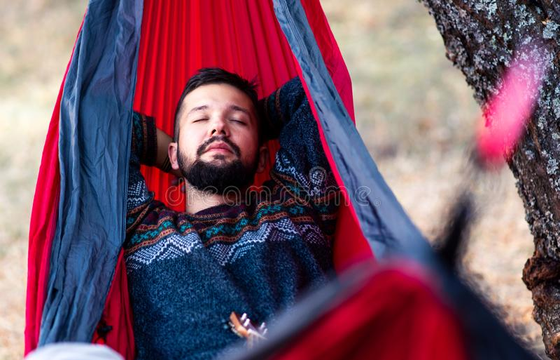 Homme détendant dans un hamac sur un pique-nique photos libres de droits