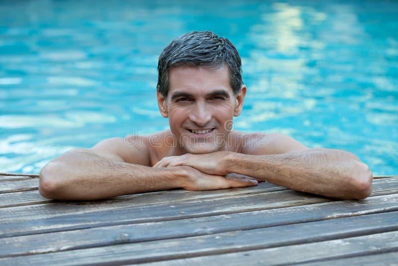 Homme détendant par le bord de la piscine photographie stock libre de droits