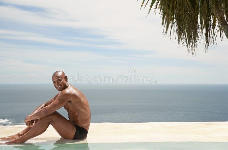 Homme détendant par le Poolside à la station de vacances photo stock