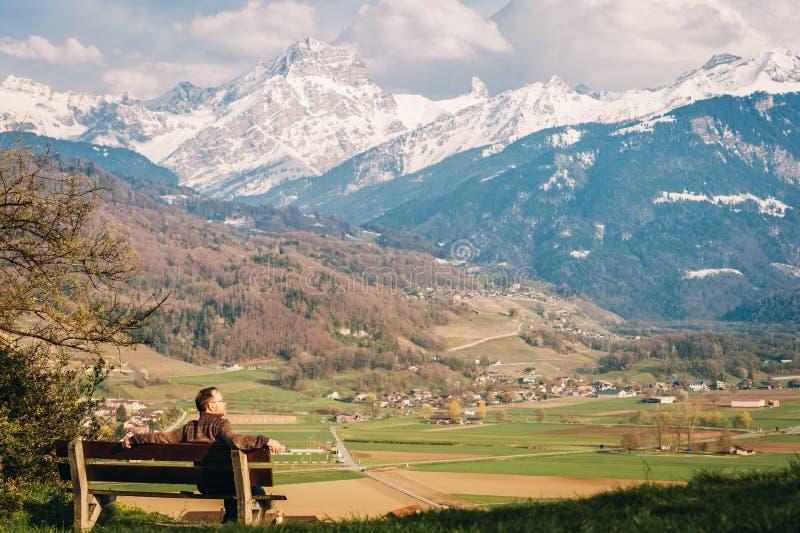 Homme détendant sur le banc, admirant les Alpes suisses photo libre de droits