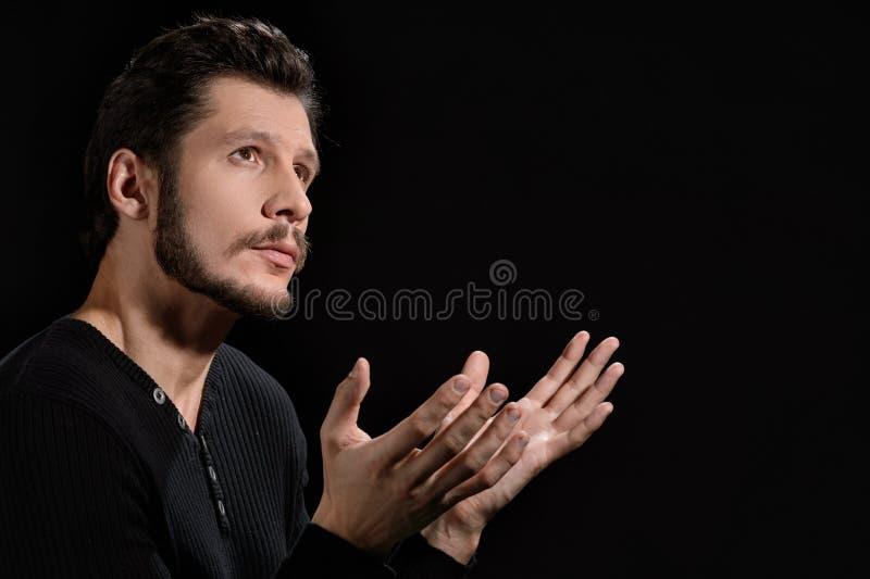Homme dévot. Portrait de l'homme barbu dévot priant et tenant h photographie stock