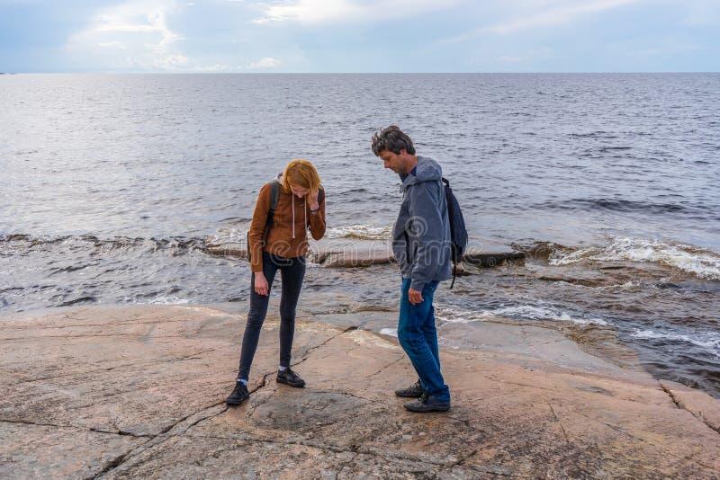 Homme d'âge moyen et jeune femme marchant sur la rive nord du lac en été Touristes à la recherche de pétroglyphes anciens Voyager photo stock