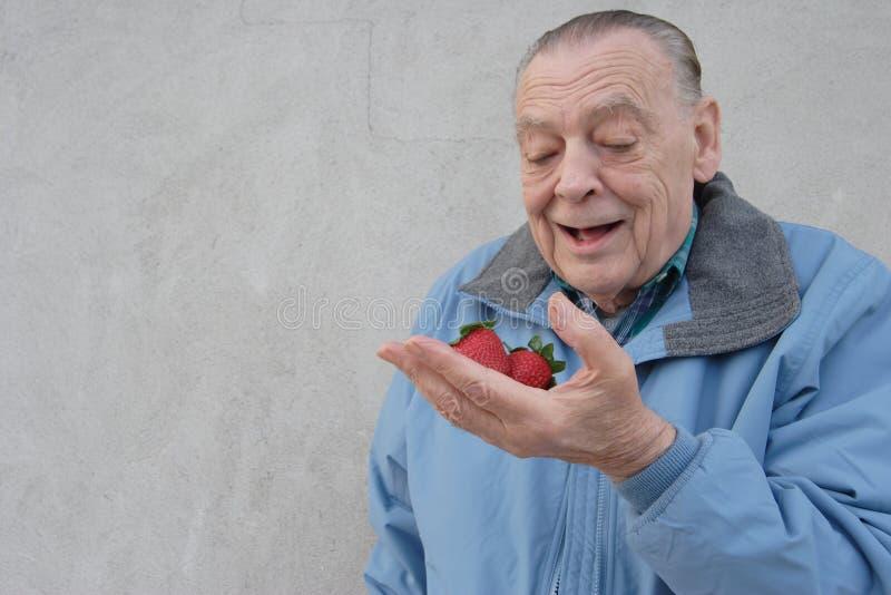 Homme d'aînés avec des fraises images stock