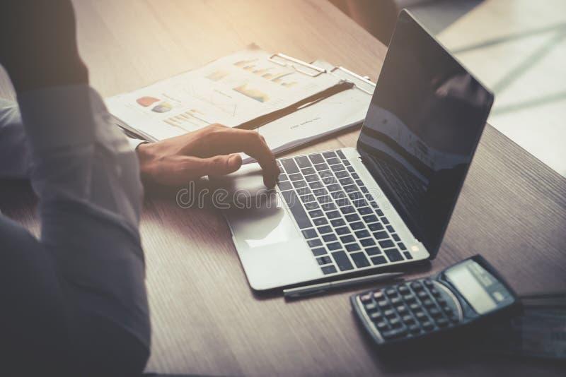 Homme d'affaires à l'aide de l'ordinateur sur la table en bois avec la calculatrice a photo libre de droits