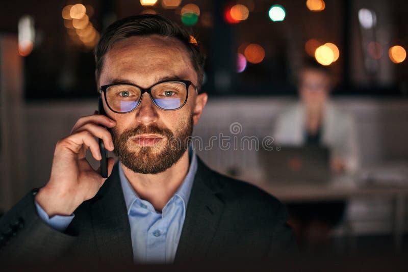 Homme d'affaires à l'aide du téléphone de fin de nuit photos libres de droits
