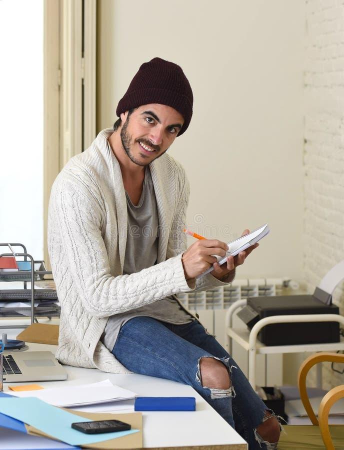 Homme d'affaires à la mode dans la calotte fraîche de hippie et l'écriture informelle de regard sur la protection fonctionnant à  photo stock