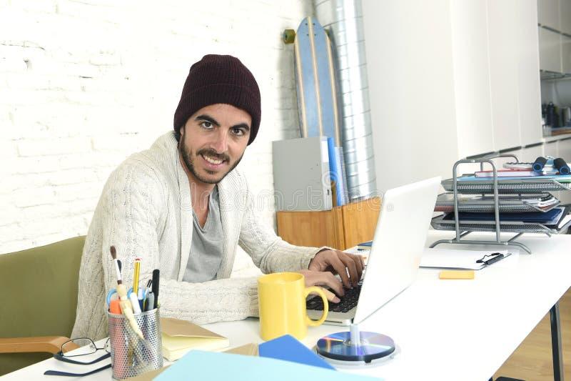 Homme d'affaires à la mode dans le travail potable de café de calotte fraîche de hippie heureux dedans au siège social moderne images libres de droits