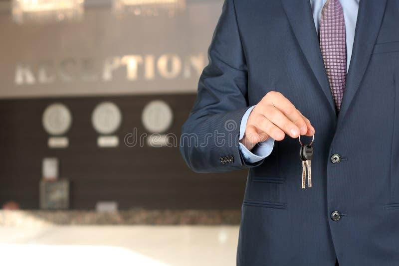 Homme d'affaires à la réception donnant des clés photos stock