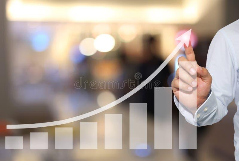 Homme d'affaires à toucher dans la crête du graphique de gestion sur la tache floue abstraite photographie stock libre de droits