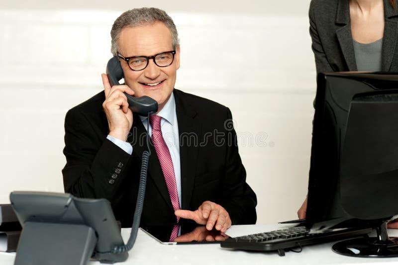 Homme d'affaires âgé communiquant au téléphone photos stock