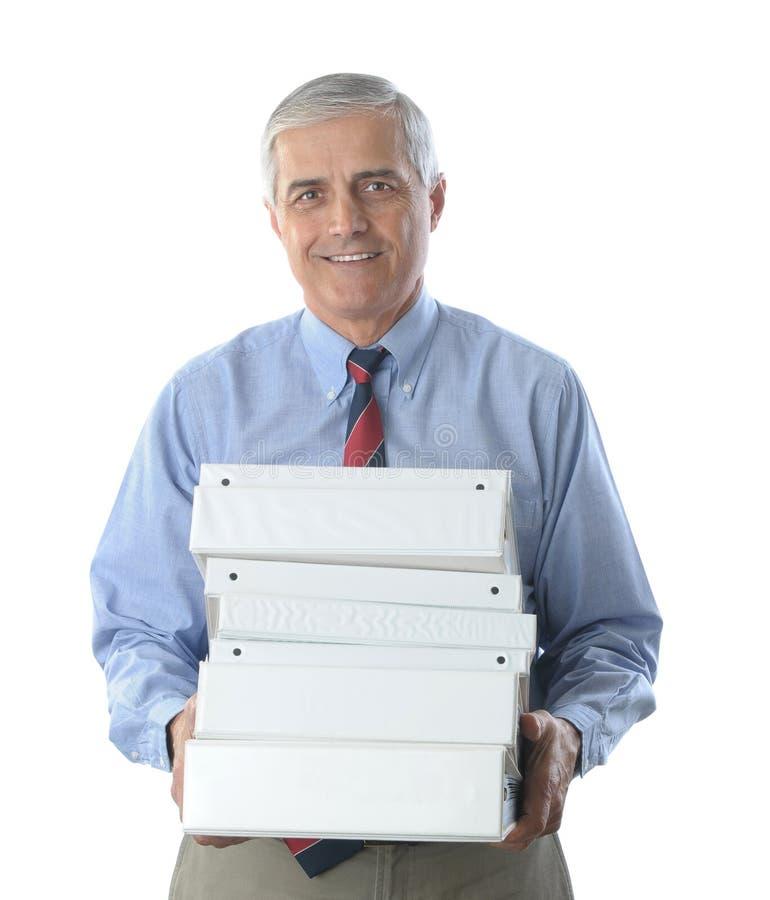 Homme d'affaires âgé moyen avec la pile de cahiers photo stock