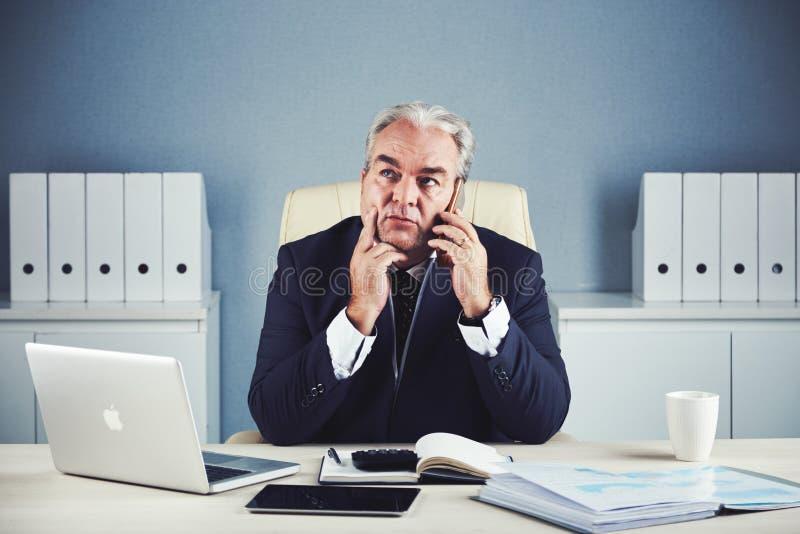 Homme d'affaires âgé songeur parlant sur le smartphone image libre de droits