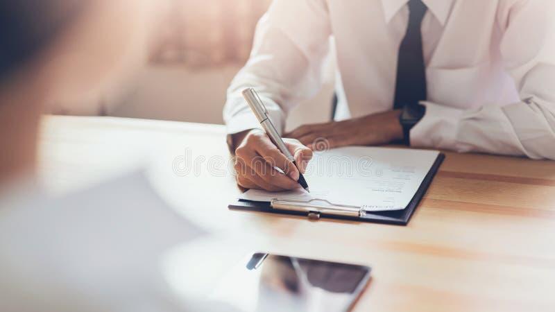 Homme d'affaires écrivant la forme pour soumettre pour reprendre l'employeur pour passer en revue la demande d'emploi images libres de droits