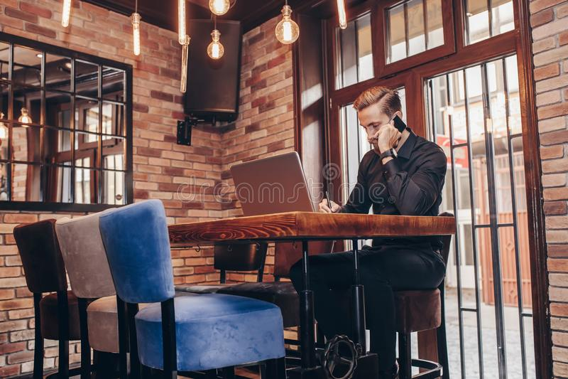 Homme d'affaires écrivant le notaire pendant la conversation de téléphone portable photos libres de droits