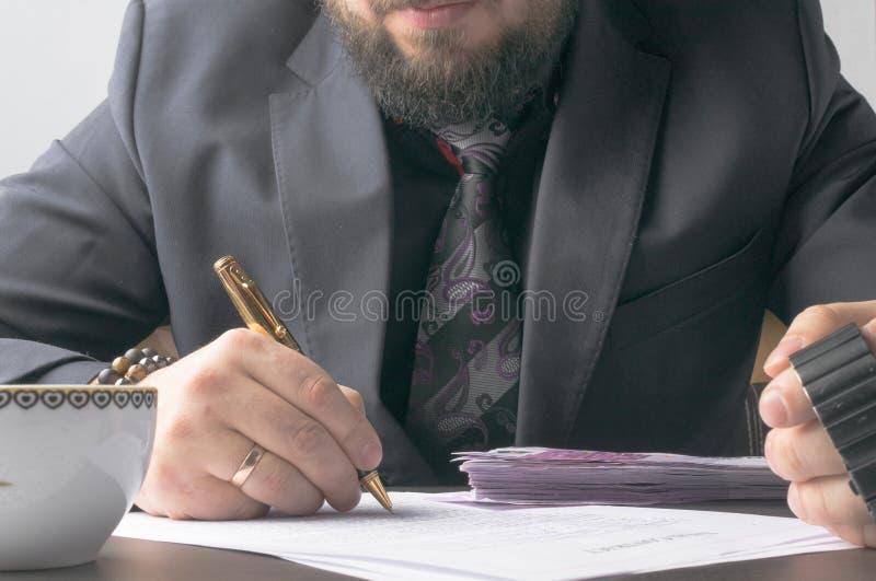Homme d'affaires écrivant un traité ou un contrat à la table et travaillant sur des documents dans le bureau, concept d'affaires image stock