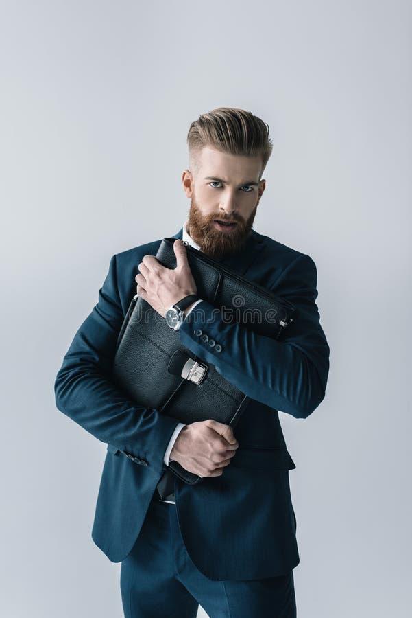 Homme d'affaires élégant étreignant la serviette et regardant l'appareil-photo photographie stock