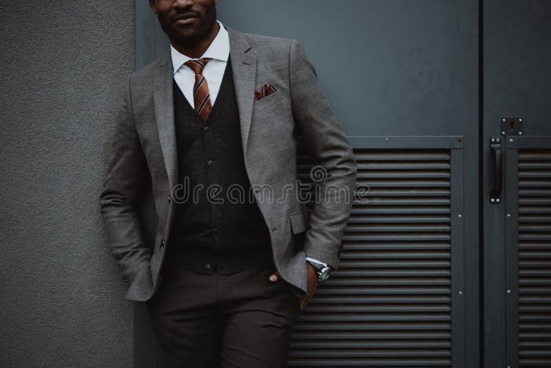 Homme d'affaires élégant d'afro-américain posant dehors au mur photographie stock libre de droits