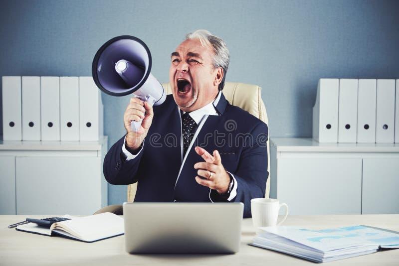 Homme d'affaires émotif supérieur criant dans le mégaphone images libres de droits