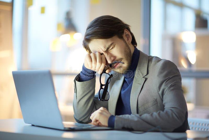 Homme d'affaires épuisé sur le lieu de travail image libre de droits