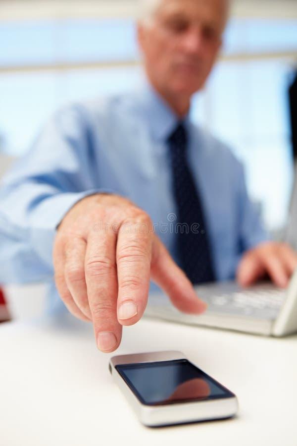 Homme d'affaires aîné avec l'ordinateur portatif et le téléphone photographie stock