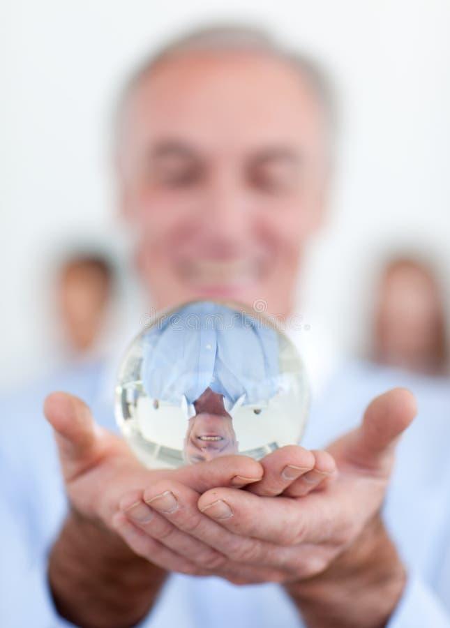 Homme d'affaires aîné retenant une bille en cristal photo stock