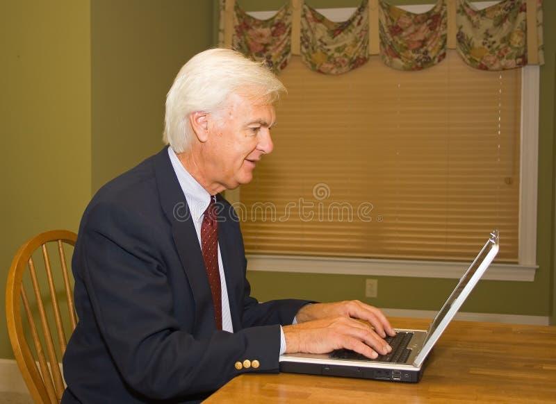 Homme d'affaires aîné sur l'ordinateur portatif photos stock