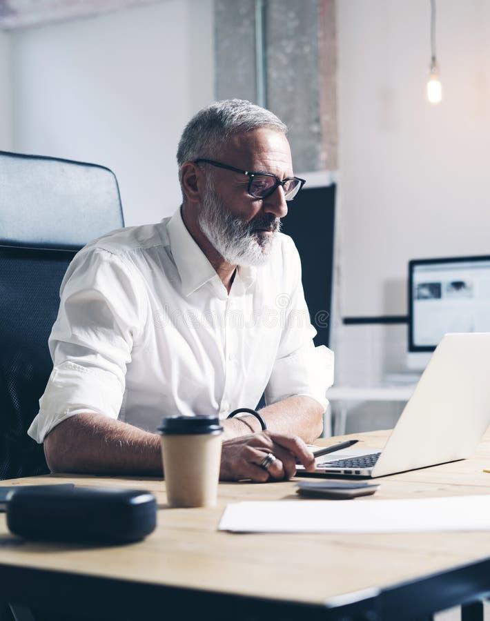 Homme d'affaires adulte attirant et positif utilisant l'ordinateur portable mobile tout en travaillant à la table en bois à moder photographie stock