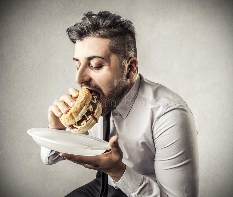 Homme d'affaires affamé pendant la pause de midi photos stock