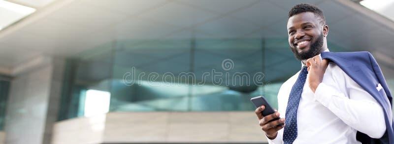 Homme d'affaires africain attirant tenant son téléphone tout en se tenant près d'un bâtiment d'étage et regardant droit devant photos stock