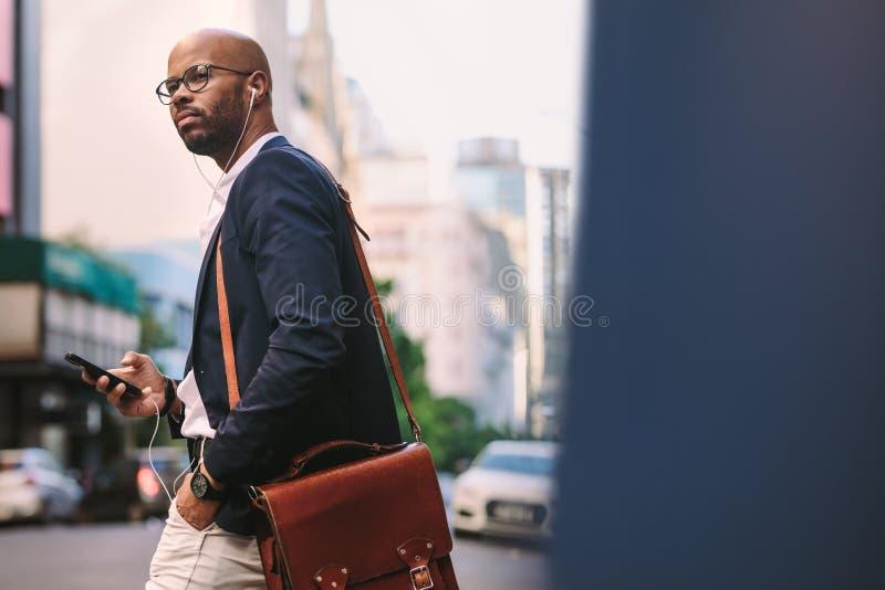 Homme d'affaires africain avec le sac marchant sur la rue photographie stock libre de droits