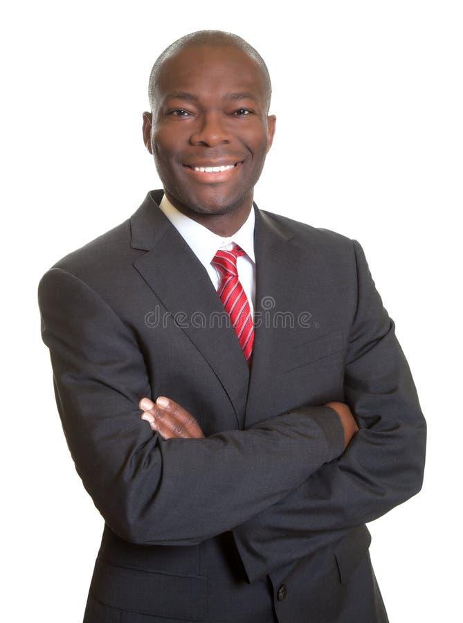 Homme d'affaires africain avec les bras croisés riant de l'appareil-photo photographie stock libre de droits