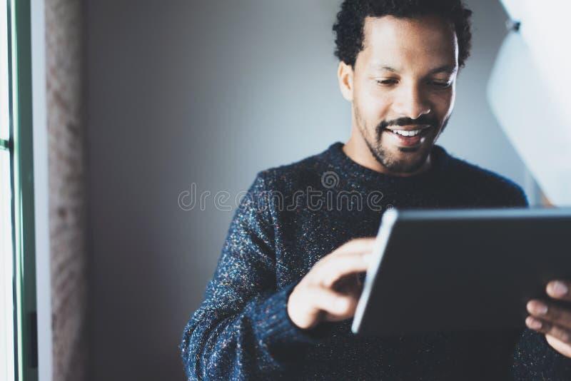 Homme d'affaires africain barbu attirant utilisant le comprimé tout en se tenant à son siège social moderne Concept des jeunes image libre de droits