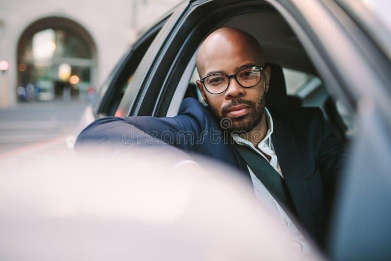 Homme d'affaires africain conduisant la voiture dans la ville photographie stock libre de droits