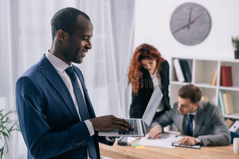 Homme d'affaires africain de sourire avec l'ordinateur portable dans travailler de mains et de deux collègues d'affaires photos stock