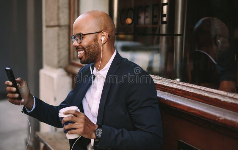 Homme d'affaires africain faisant un appel visuel avec le smartphone photos stock