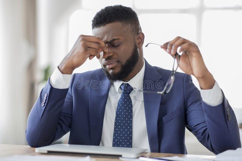 Homme d'affaires africain frustrant massant son nez dans le bureau photo stock