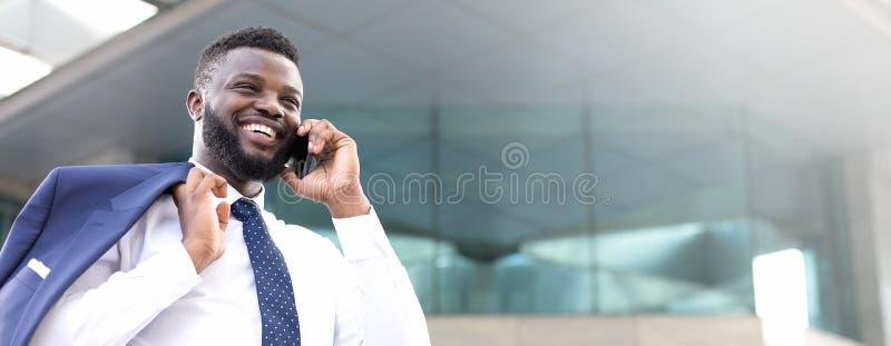 Homme d'affaires africain heureux tenant son téléphone tout en se tenant près du bâtiment et regardant droit devant image stock
