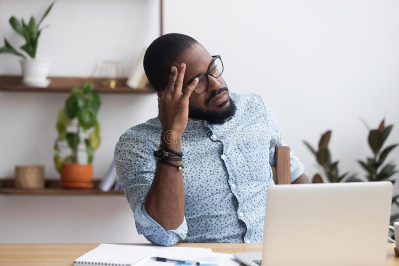Homme d'affaires africain réfléchi sérieux s'asseyant au bureau image stock