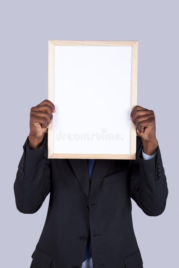 Homme d'affaires africain retenant un whiteboard photographie stock libre de droits
